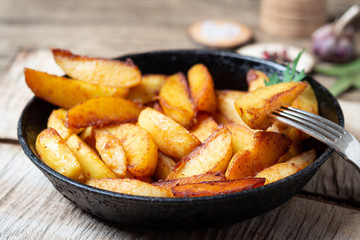 Fried potatoes wedges in a pan on wooden table.