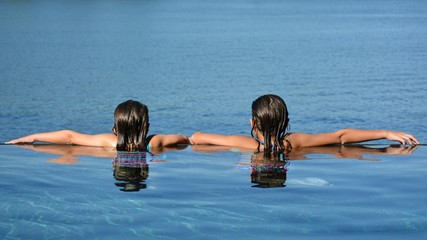 Two girls at edge of lakeside infinity pool looking to the water beyond