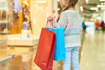 Rear view portrait of cute little girl holding big paper shopping bag standing against window display, copy space
