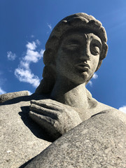 statue of an angel with his arms crossed against a blue sky. The angel in prayer. Stone angel in colour.