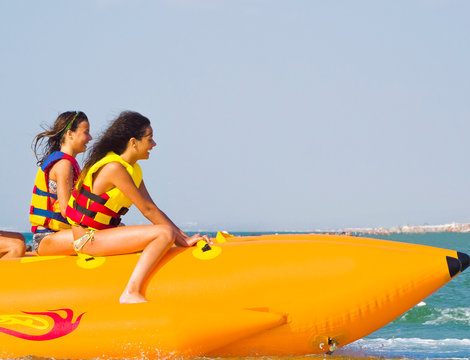 extreme speed attraction in the sea.ea attraction. Group of young enjoying a ride on a banana boat on sunny summer day. Beach water sport