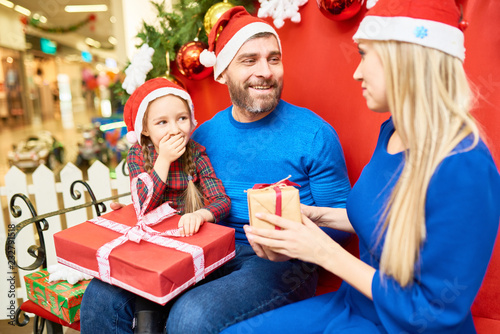 be747902eb276 Smiling man and woman with little daughter in Santa hat giving presents to  each other celebrating Christmas