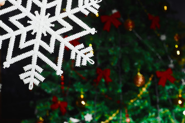 Big snowflake on a decorated Christmas tree background with copy space for your text