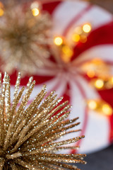 Christmas gold glitter ornament on red and white swirl design with bokeh lights background