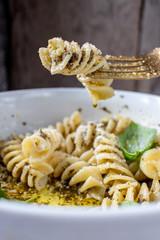 Fusilloni spiral pasta with pesto and parmesan in white bowl