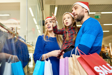 Adult parents and little girl in Santa hat carrying bags and exploring window shop in mall preparing for holiday