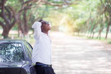 African businessman wearing a white shirt and black glasses stands smiling at the car with happy and relax