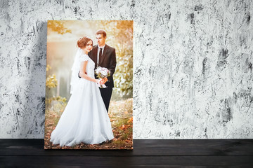 Photo of a wedding couple printed on canvas. Photography with stretch on a wooden frame on a white wall background with copy space