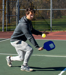 Young man playing pickleball paddle sport