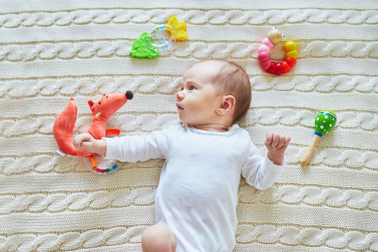 Newborn baby girl with colorful wooden toy