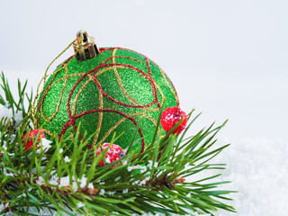 Green Christmas ball and fir branches on the snow. Christmas background
