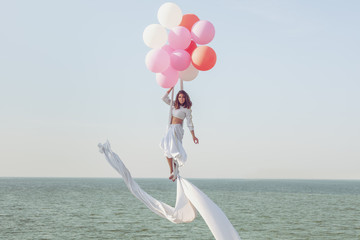 Young woman in a white suit hovers in the air.