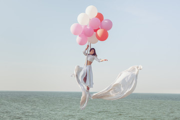 Young woman flying in the air by balloons.