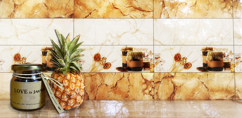 Close-up image from a Kitchen Interior Scene with Orange and White wall tiles, with Pineapple and a Honey jar