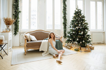 Christmas concert. Cute blonde girl in an evening dress opens beautifully packaged gifts lying under the tree on the background of a cozy living room in white.