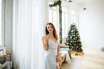 Christmas concert. Cute blonde woman in evening dress holding a glass of sparkling champagne on the background of a large beautifully decorated Christmas tree in the living room.