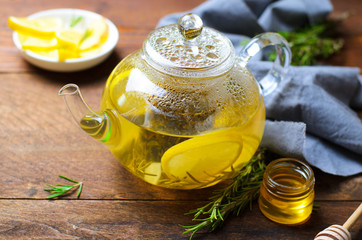 Healthy Ginger Tea with Lemon and Rosemary in Glass Teapot on Dark Wooden Background