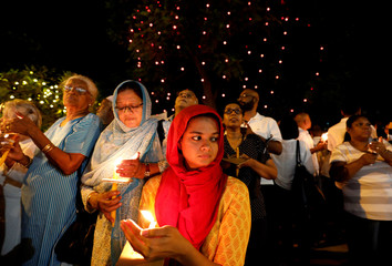 Women hold candles during a vigil campaign demanding democracy in the country, in Colombo
