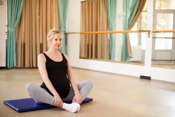 Young beautiful pregnant woman on yoga, pilates and ballet class