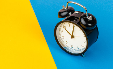 Black alarm clock on color block yellow and blue background