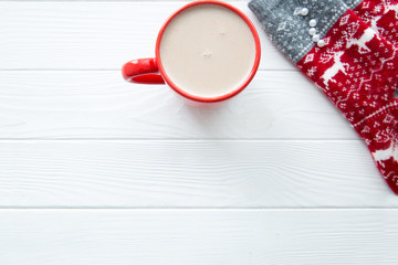 Red cup of hot cacao and Christmas sock with ornament and deer. Free space for text.