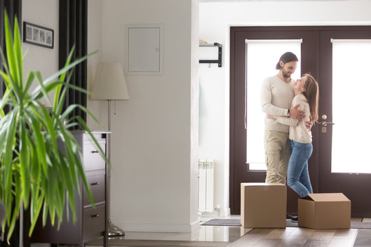 Young married satisfied couple standing in hallway, arrive at new house with cardboard boxes. Glad wife and husband hugging feel happy buying new dwelling. Relocation, moving mortgage or loan concept