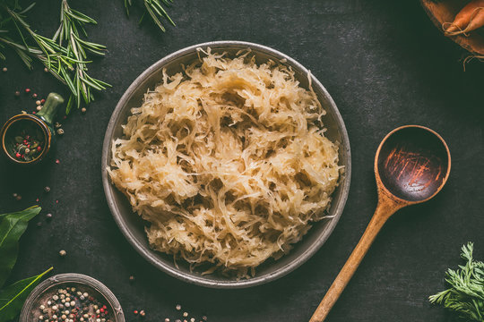 Pickled cabbage in bowl with wooden spoon and seasoning on dark rustic kitchen table background, top view. Vegetarian clean food. Paleo diet. Healthy eating concept