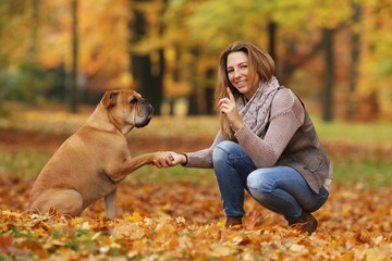 Middle age woman doing tricks with her dog