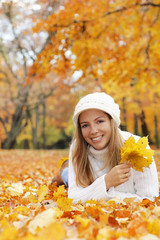 Happy middle age woman lying on the ground with autumn leaves