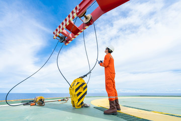 Mechanical crane inspector inspect crane system as annual preventive maintenance schedule, He's test and check hook, cable, sleeve and hydraulic system. Offshore operation.