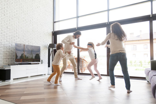Happy funny family with little preschool son and daughter enjoying spending free time on weekend at new modern home. Playful, small boy with covered eyes playing hide and seek together in living room