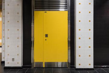 Yellow door with metal trim and tile walls