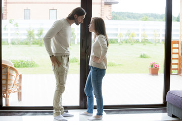 Dissatisfied husband and wife standing opposite panoramic window at home looking at each other with angry and quarrelling. Break up, difficulties and misunderstanding in relations concept, full length