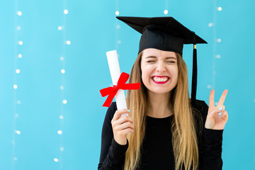 Young woman with a graduation diploma on a shiny light background