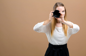 Young woman with a professional digital SLR camera on a brown background
