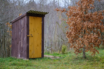 old wooden countryside toilet house with heart shaped hole in the door