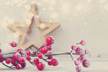 red an white christmas - twig with berries close up and star on aged wooden background, retro toned