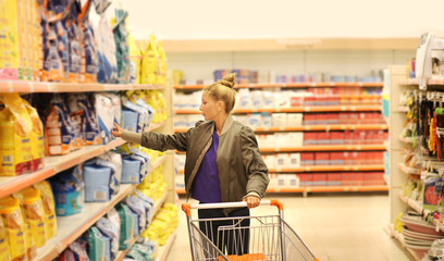 Woman choosing a dairy products at supermarket.Pet Food