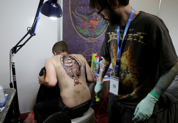 A man displays a tattoo on his back during the Art Tattoo Convention in La Paz
