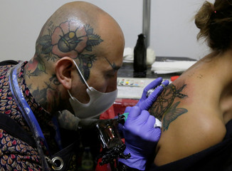 A tattoo artist tattoos a woman during the Art Tattoo Convention in La Paz