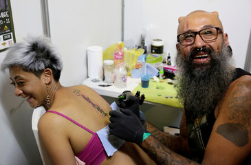 A tattoo artist smiles while tattooing a woman during the Art Tattoo Convention in La Paz