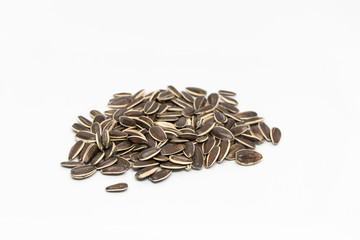 Black large seeds on a white background. Sunflower seeds are gray with white stripes, a handful.