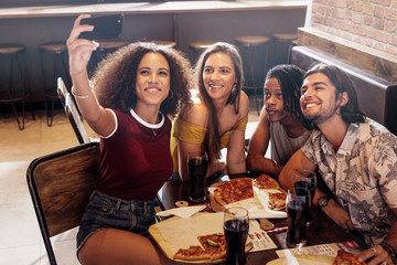 Woman taking selfie with friends at restaurant