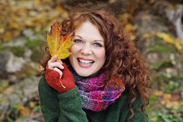 jeune et jolie femme rousse souriante aux yeux bleus dans nature en automne