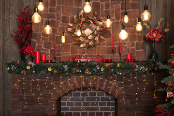 Brick fireplace is decorated with a Golden wreath and a sparkling Christmas garland with Christmas decorations
