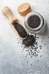 Black cumin seeds on a wooden spoon and in a glass jar on gray background