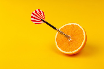 orange slice, fruit with circular target marked and dart on yellow background. minimal idea food and fruit concept. Idea creative to produce work and advertising marketing communications