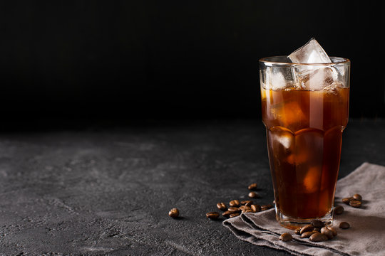 tall glass cold brew coffee with ice on black or dark background