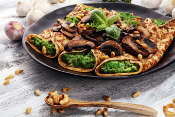 Savory Homemade Mushroom and Spinach Crepes with Cheese and avocado.