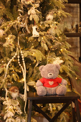 New Year and Christmas photos for advertising, postcards, posters and banners, magazines and newspapers. Toy bear near the Christmas tree.